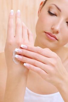 Giovane bella donna che applica crema cosmetica sulle mani