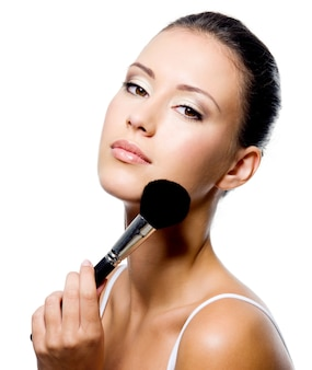 Giovane bella donna che applica polvere sullo zigomo con la spazzola - isolata