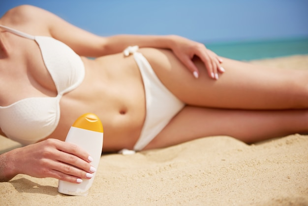 Young beautiful woman applying sun cream on the beach