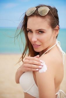 ビーチで日焼け止めクリームを塗る若い美しい女性