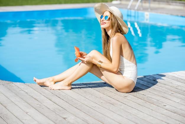 木製のプールサイドに座って日焼け止めローションを適用する若い美しい女性。日焼け止めソーラークリームuv保護コンセプト
