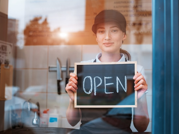 Young beautiful woman in an apron a cafe worker holds a sign open against the background of a bistro behind the glass window