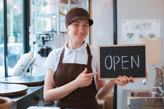 Young beautiful woman in an apron a cafe worker holds a sign open against the background of a bistro