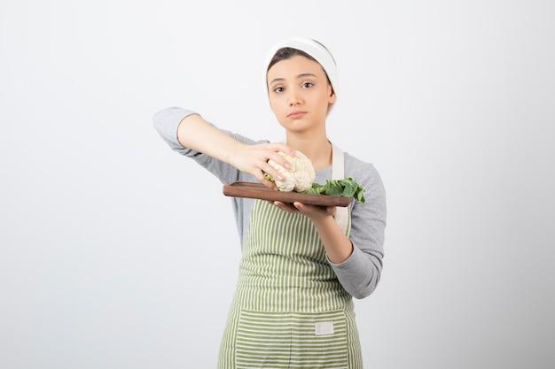 Giovane bella donna in grembiule che tiene piatto di cavolfiore