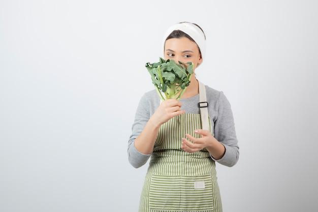 Giovane bella donna in grembiule in posa con broccoli freschi su bianco