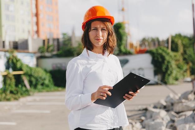 Архитектор молодой красивой женщины в белой рубашке и каске, держа доску сальто. женщина в каске на строительной площадке у себя дома.