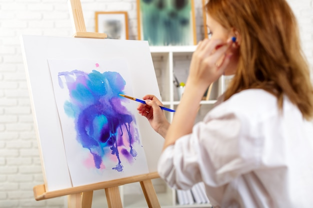 Young beautiful woman artist drawing abstract painting on an easel