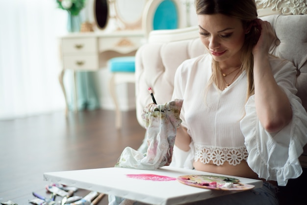 Young beautiful woman artist painting at home pink peonies