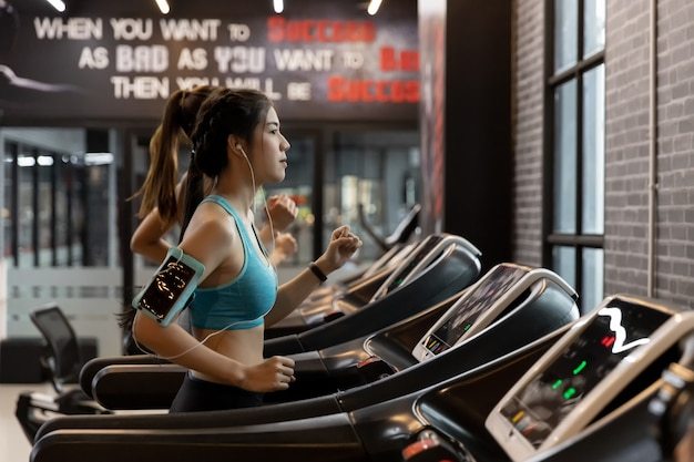 Young beautiful woman asian running on a treadmill at gym.
