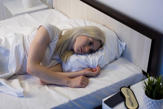 Молодая красивая женщина в домашней спальне, лежа в постели поздно ночью, пытается заснуть, страдая бессонницей