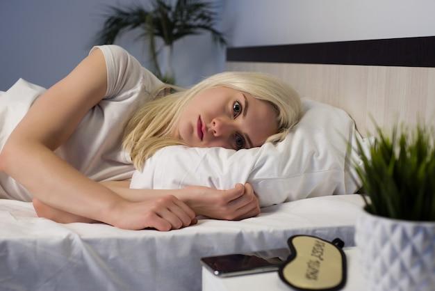 不眠症に苦しんで眠ろうとして夜遅くベッドに横たわっている自宅の寝室で若い美しい女性