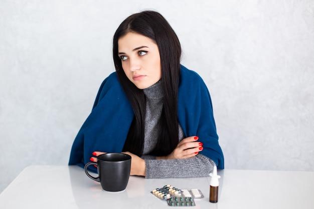 風邪や気管支炎の症状として気分が悪く、咳をしている白いテーブルに自宅で若い美しい女性。ヘルスケアの概念。