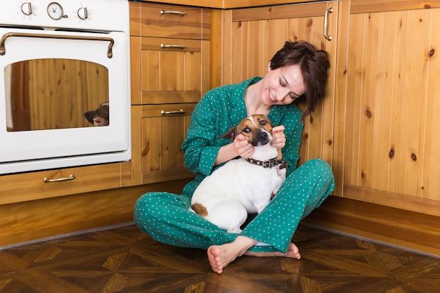 彼女のかわいい犬と一緒に家で若い美しい女性
