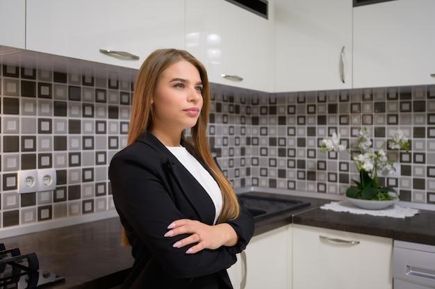 きれいなデザインの豪華なモダンな黒と白のキッチンインテリアで若い美しい女性