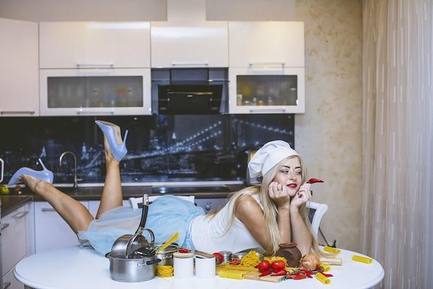 セクシーなイタリア料理のセクシーな準備をしている台所のテーブルで若い美しい女性