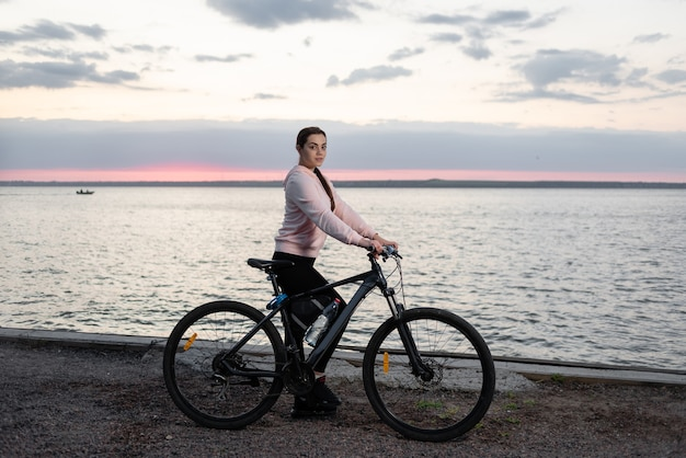 Young beautiful woman, an athlete with a bicycle, from early morning looks at the dawn over the sea and rests from a bike ride.