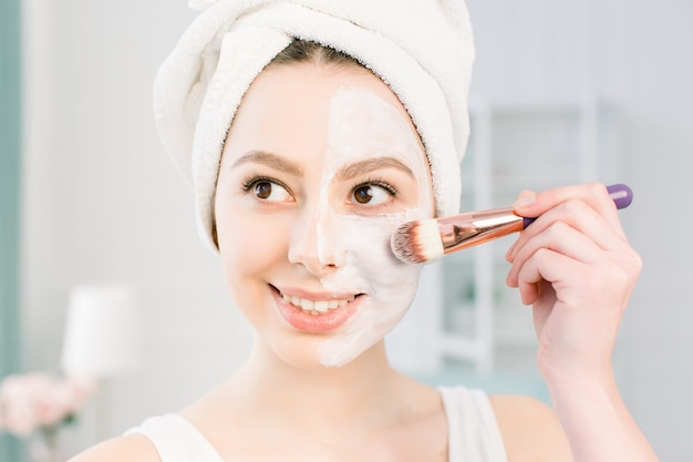A young beautiful woman in a bathing towel after a shower and cleansing the skin applies a clay mask to the face with a cosmetic brush. beauty, health, cosmetology concept. lifestyle. skin care