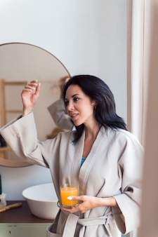 Young beautiful woman in bathrobe holding orange juice glass self care concept