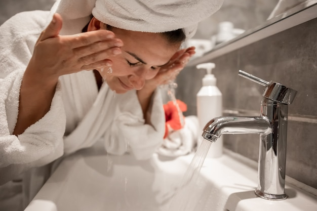 Young beautiful woman in the bathroom with a towel on her head washes her face with tap water