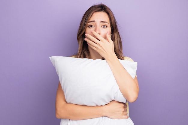 Giovane bella donna in maglietta beige che tiene un cuscino bianco che guarda la telecamera scioccata che copre la bocca con la mano