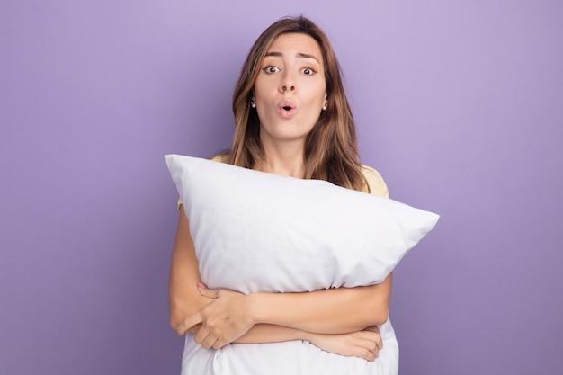 Giovane bella donna in maglietta beige che tiene un cuscino bianco che guarda la telecamera sorpresa in piedi sul viola