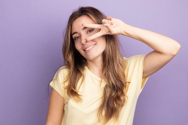 Giovane bella donna in maglietta beige che guarda l'obbiettivo felice e allegra sorridente che mostra il segno v vicino al suo occhio in piedi su sfondo viola