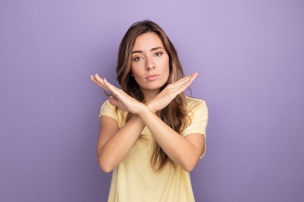 Giovane bella donna in t-shirt beige che guarda la telecamera con una faccia seria che fa un gesto di arresto incrociando le mani in piedi su sfondo viola