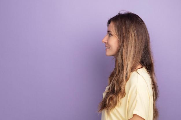 Giovane bella donna in maglietta beige in piedi di lato con un sorriso sul viso su sfondo viola