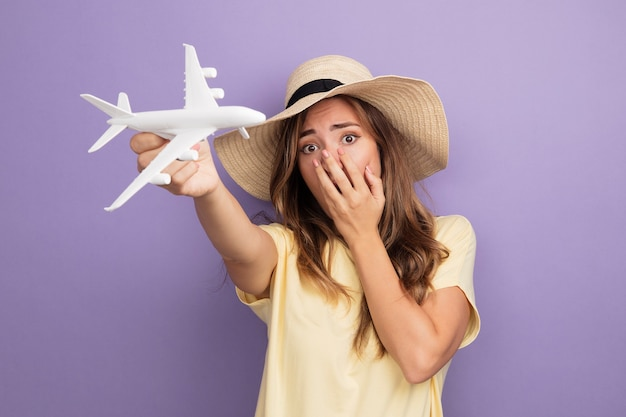 Young beautiful woman in beige t-shirt and summer hat holding toy airplane looking at camera being shocked covering mouth with hand standing over purple background
