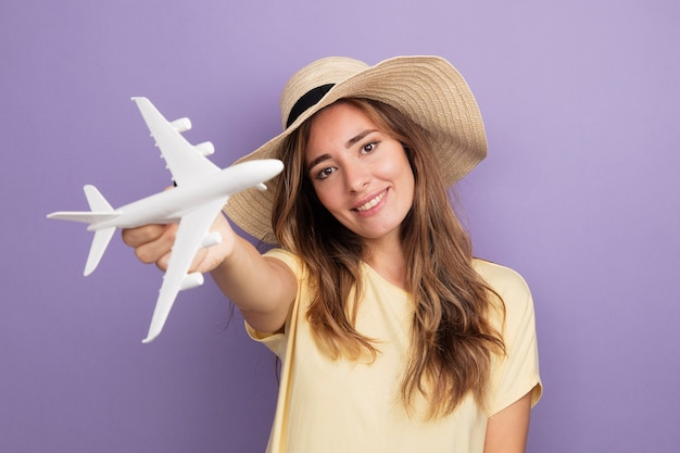 Young beautiful woman in beige t-shirt and summer hat holding toy airplane looking at camera with smile on face standing over purple background