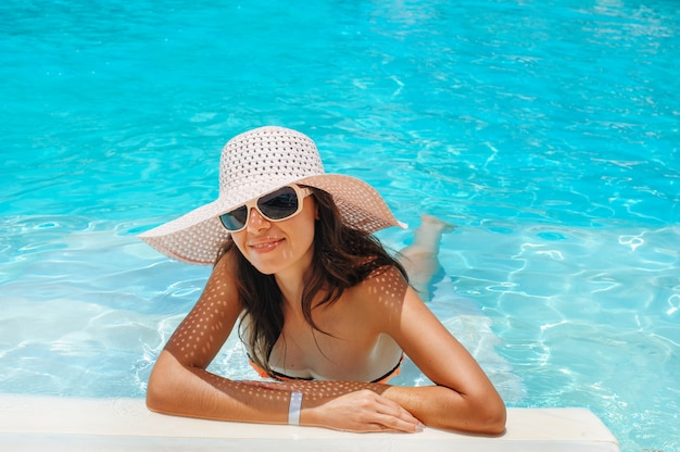 Young beautiful woman in big white hat on edge of the pool