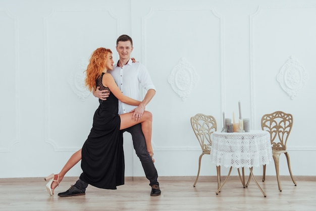 Young beautiful woman in a black dress and a man in white shirt dancing.