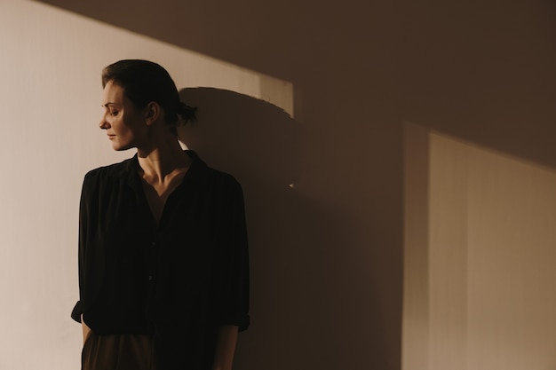 Young beautiful woman in black shirt and brown trousers staying against the wall.