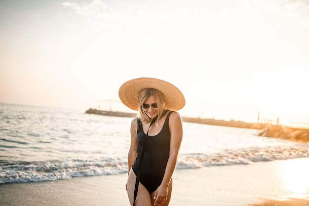 Young beautiful woman in a black swimsuit and hat with glasses walks along the beach in turkey at sunset. the concept of sea recreation. selective focus