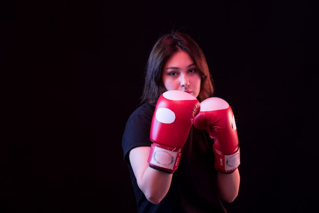 Young beautiful woman in black t-shirt and red boxing gloves