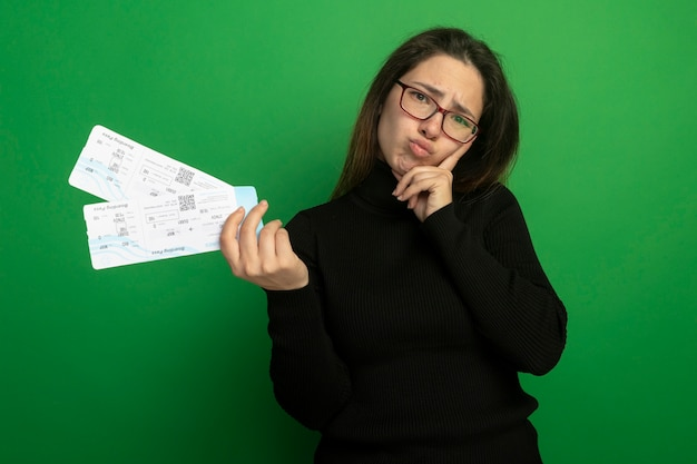Young beautiful woman in a black turtleneck and glasses holding air tickets looking at front being confused and displeased standing over green wall