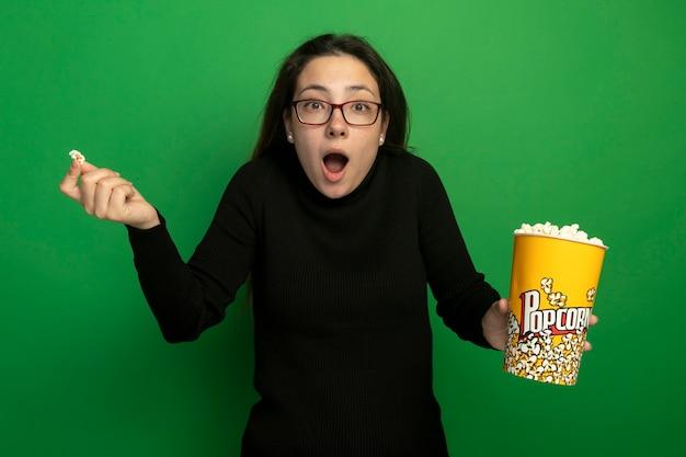 Giovane bella donna in un dolcevita nero e bicchieri tenendo la benna con popcorn guardando confuso con il braccio sollevato in piedi sopra la parete verde