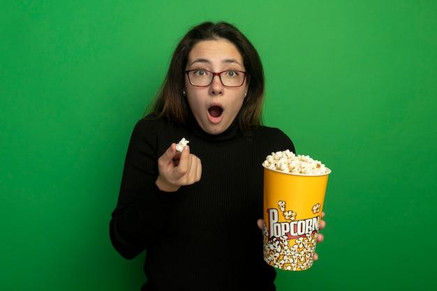 Giovane bella donna in un dolcevita nero e bicchieri tenendo il secchio con popcorn guardando davanti stupito e sorpreso in piedi sopra la parete verde