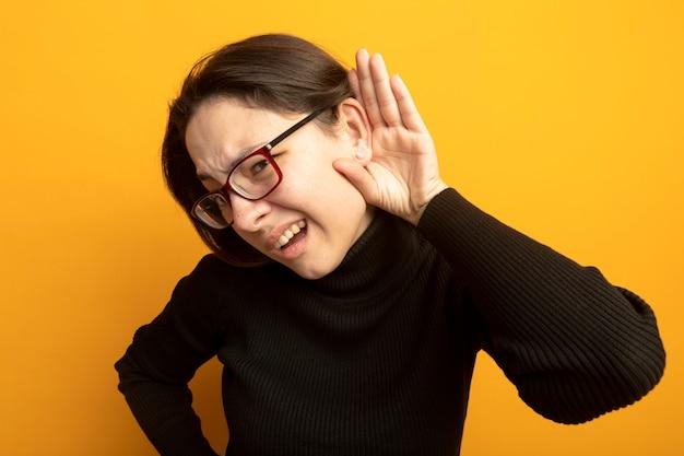 Giovane bella donna in un dolcevita nero e occhiali tenendo la mano vicino al suo orecchio cercando di ascoltare pettegolezzi in piedi sopra la parete arancione