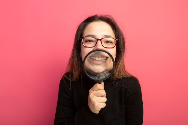 Young beautiful woman in a black turtleneck and glasses holding magnifying glass in front of her smile standing over pink wall
