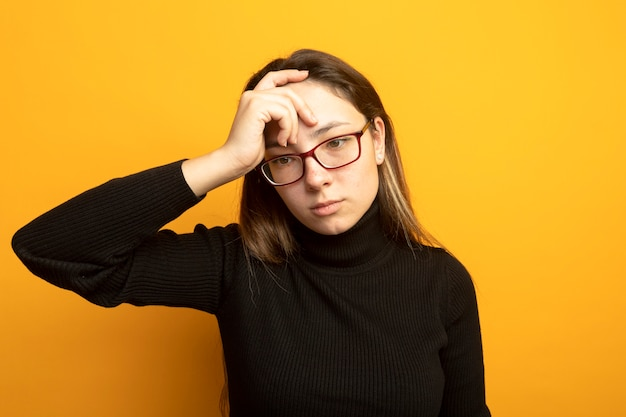 Young beautiful woman in a black turtleneck and glasses looking aside puzzled with hand on her head standing over orange wall