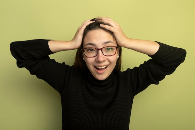 Giovane bella donna in un dolcevita nero e occhiali guardando davanti pazzo felice mano nella mano sulla sua testa in piedi sopra la parete chiara