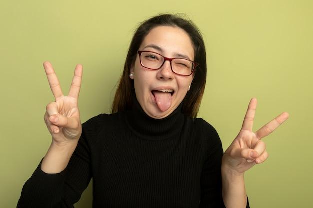Giovane bella donna in un dolcevita nero e occhiali guardando davanti felice e positivo che mostra v-segno spuntavano lingua in piedi sopra la parete leggera