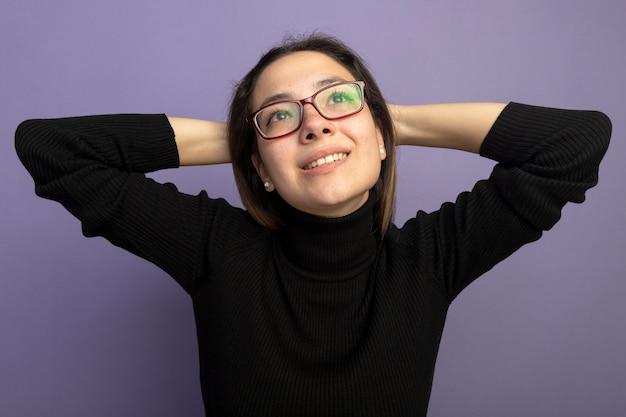 Giovane bella donna in un dolcevita nero e occhiali che osserva in su con le mani alzate rilassarsi e sognare di provare emozioni positive in piedi sopra il muro viola