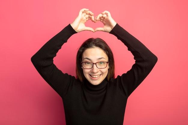 Giovane bella donna in un dolcevita nero e occhiali che fa il gesto del cuore sopra la sua testa sorridendo allegramente in piedi sopra il muro rosa