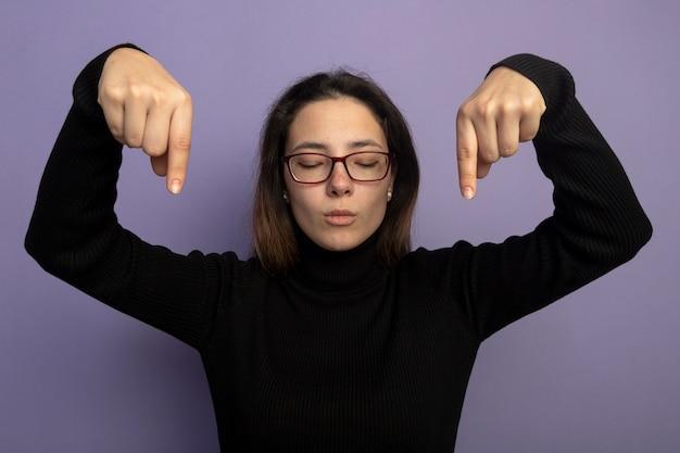 Giovane bella donna in un dolcevita nero e occhiali rivolti con il dito indice verso il basso con la faccia seria con gli occhi chiusi in piedi sopra il muro viola