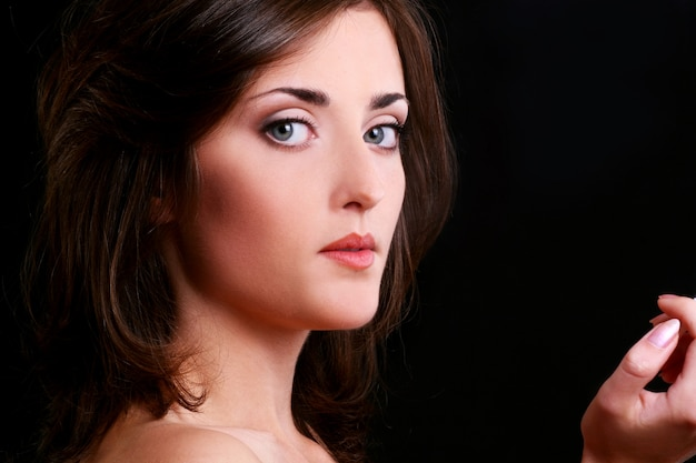 Young and beautiful woman on black