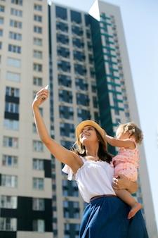 小さな娘と都市の風景の中で自分撮りを作る夏服の若い美しい女性ブロガー