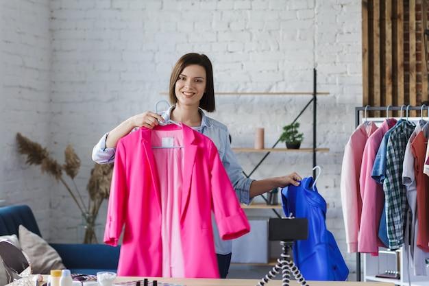 Молодая красивая женщина-блоггер показывает одежду на камеру