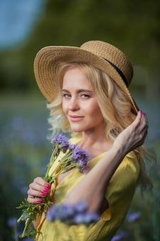 모자에 젊은 아름 다운 여자 금발 보라색 꽃의 필드를 안내합니다. 여름. 봄.